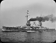 A large gray battleship steams ahead. Dark black smoke pours from its two funnels.