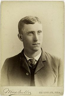 A black-and-white photograph of a man wearing a dark Victorian-style suit and tie