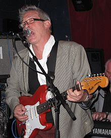 Jankel singing into a microphone onstage
