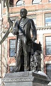 Estátua de bronze de um homem em um parque da cidade