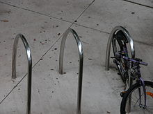 Three stainless steel U-rings set in concrete, without bolts. A bicycle is chained to the one on the right.