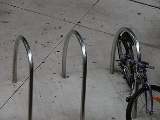 Три U-образных кольца из нержавеющей стали в бетоне без болтов. Велосипед прикован цепью к тому, что справа.