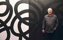 Corey Postiglione, in front of his black-and-white, site-specific painting, Population 5, at his exhibition of the same name.