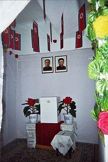 Urna nordcoreana in cui, sotto le bandiere dello stato, si intravedono i ritratti di Kim Il-sung e di Kim Jong-il