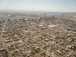 Aerial view of downtown Long Beach, California, looking southwest. San Pedro Bay and the Port of Long Beach are visible beyond, with Catalina Island faintly visible on the horizon.