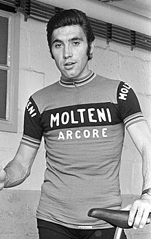 "Merckx holding a bicycle. His shirt says ""Molteni Arcore"", and his hair is slicked back."