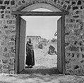 Een franciscaner monnik bij een geopende poort met het gezicht op de deels gerec, Bestanddeelnr 255-1547.jpg