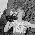 Erika Klein poseert met glas moezelwijn voor een muur begroeid met druiven, Bestanddeelnr 254-4640.jpg