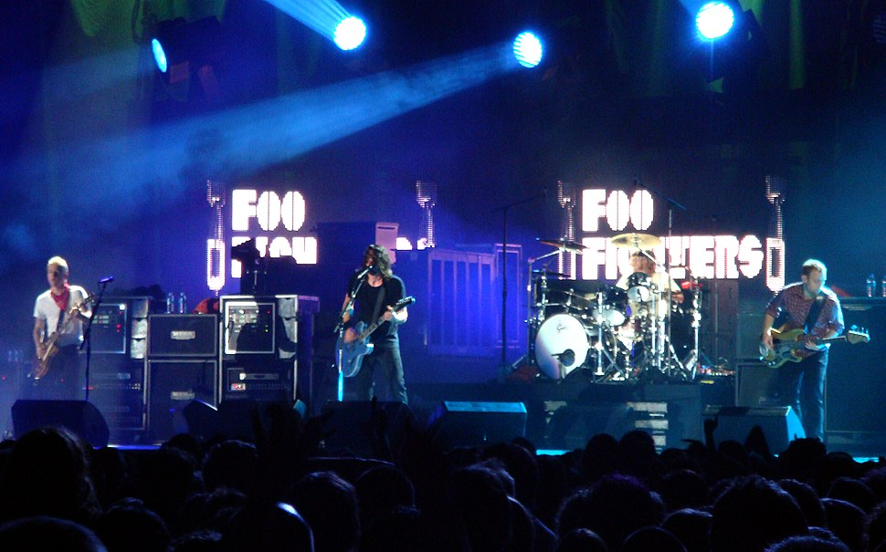 Four men performing on a stage in front of a crowd; three are standing at the front of the stage holding guitars, while one is sitting behind a drum set. Audio equipment, microphone stands, and lighting can also be seen on the stage and in the background.
