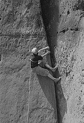 Un grimpeur gravissant une fissurant avec une corde autour du torse
