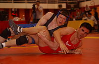 The freestyle wrestler in the blue singlet scores points over the wrestler in the red singlet to win by decision.