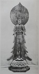 Front view of a standing statue with flowing robes holding a small container in front of her body. There is a large halo behind the head of the statue.
