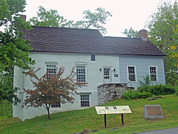 A two-story house in two sections, both with side-gabled shingled roofs, built into a slope towards the right that exposes the basement on the left. The left three bays, including the main entrance with a stone step, is faced in stucco and painted a bluish-grey; the right is wooden and painted light blue. In front there is a memorial plaque on stone and a modern interpretive plaque.