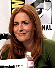 A woman with red hair looks past the camera and smiles.