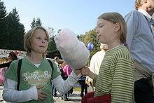 Due bambini assaggiano lo zucchero filato.