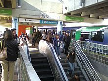 A busy metro station during rush hour with many passengers leaving the train and exiting the station.