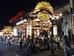 A festival float cart with taiko drummers lit up at night