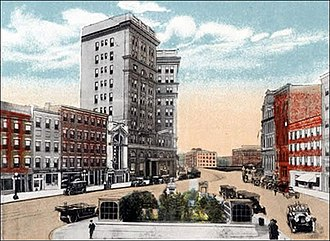 Hanover Square, Syracuse - Hanover Square in 1910 - Horsedrawn carriage on Water Street to the right. In the foreground, the small, former Veterans Park displays the entrances to the underground restrooms, which were demolished in 1962