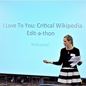 Monika Sengul-Jones is standing in front of a large screen displaying the text I Love To You: Critical Wikipedia Edit-a-thon, Welcome.