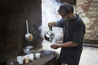Chaiwala - A chaiwala in Varanasi pouring a cup of chai.