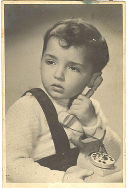 Jacob Rubinovitz as a child, holding a white phone toy.