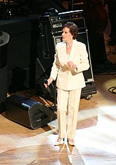 A dark-haired woman wearing a white jacket and pants, standing on a stage