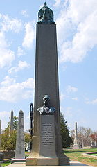 A large obelisk in a graveyard, with a bust of Tyler. The black structure visible behind the left side of Tyler's obelisk encloses the grave of James Monroe.