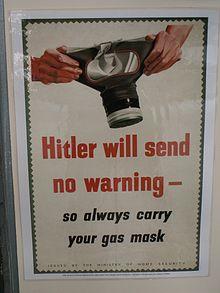 Photo en couleurs d'une affiche publiée par le ministère de la Sécurité civile anglais pendant la Seconde Guerre mondiale. Sur un fond vert foncé, un rectangle de couleur blanc cassé et aux bords dentelés comme un timbre, présente, en son centre, en gros caractères rouges le message: «Hitler will send no warning». Le message est suivi par la phrase en caractères noires: «so always carry your mask». L'avertissement est illustré, en haut de l'affiche, par le dessin d'un masque à gaz tenu par deux mains.
