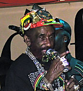 A man singing into a microphone; he is wearing a colorful hat with many accessories on his hat and around his wrists, fingers and neck.