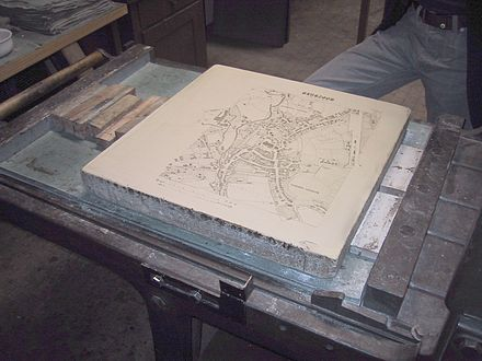 A limestone plate with a negative map of Moosburg in Bavaria is prepared for a lithography print. Litography press with map of Moosburg 01.jpg