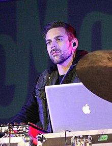 A Caucasian male with earbuds and a black leather jacket staring at an off screen entity with a MacBook laptop in the foreground