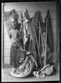 Maori carved figure wearing a piupiu and tiki, standing against a wall with weapons and cloaks. ATLIB 273584.png