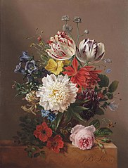 Tulips, roses, peonies and other flowers in a vase on a stone ledge