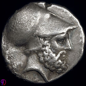 Leucippus - Bearded head with Corinthian helmet, thought to be of Leucippus, sitting dog (Molossian hound?) on the reverse.