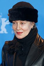 A woman in her sixties is seen wearing a leather jacket and a black hat.