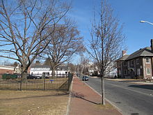 A color photo. Down the middle runs a tree-lined sidewalk, with a fenced grassy area to the left and a street to the left, lined with houses.