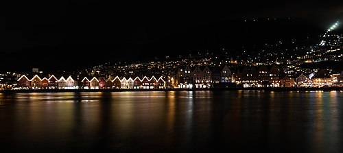 Picture of Bryggen from the opposite pier during night time. On the upper right side (hidden by fog) the Fløibanen up to Mt. Fløyen.
