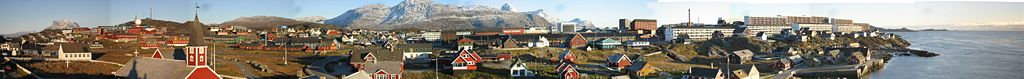 A panoramic photo compilation of Nuuk, Greenland as seen from a hill near the statue of Hans Egede in the old colonial part of town. The mountain Sermitsiaq is seen in the background all the way to the left, Store Malene directly behind the city, and Kingigtorssuaq can be seen behind it to the right