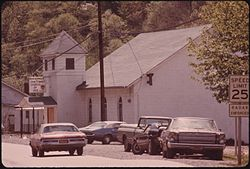 ONE OF THE ENTRANCES TO CHATTAROY, WEST VIRGINIA, NEAR WILLIAMSON, LEADS PAST A CHURCH OF GOD. THERE ARE MANY SMALL... - NARA - 556460.jpg