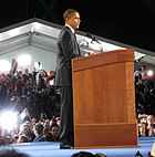 Obama delivers a speech at a podium while several flashbulbs light the background.