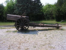 an artillery piece with no gun shield standing on gravel