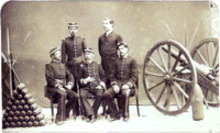 A photograph depicting a group of 5 uniformed men posed between a pyramid of artillery shells on the left and a wheeled field artillery piece on the right