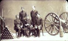Uma fotografia que descreve um grupo de 5 homens uniformizados colocados entre uma pirâmide de artilharia à esquerda e uma peça de artilharia de campo rodas à direita