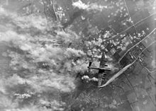 A British bomber aircraft flies over a heavily bombed agricultural landscape with many craters and plumes of smoke visible immediately below