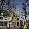 Overzicht op hoekpand met natuurstenen spekbanden en een geveltop met obelisken en een fronton - Haarlem - 20407048 - RCE.jpg
