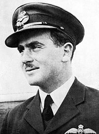 Informal head-and-shoulders portrait of dark-haired, moustachioed man in dark military jacket with pilot's wings on left breast pocket, and peaked cap