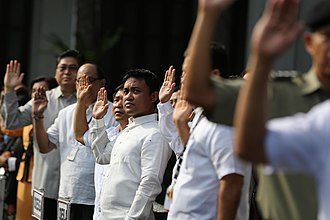 Flag of the Philippines - Government employees and officials raising their right hand for the pledge of allegiance to the Philippine flag.