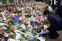 A woman adds a flower arrangement to a large memorial display set against a fence.