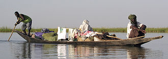 Economy of Mali - A pirogue carrying two passengers on the River Niger at Gao in Mali.