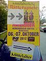 Plakat Mittelalterliche Ritterspiele im Georgengarten in Hannover vor parkenden Automobilen in der Jägerstraße, Mittelalter Oktober 2012.jpg